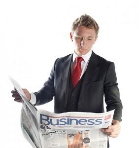 Imagen de un directivo de chaqueta leyendo el periódico